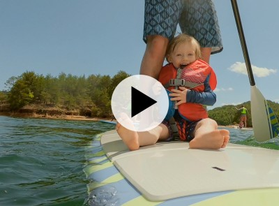 Toddler in a life jacket sitting on a stand up paddle board with a parent.