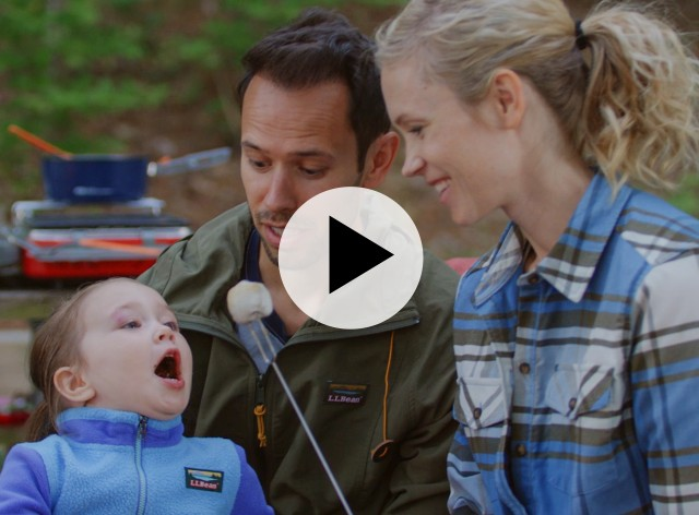 A mom and dad with toddler outside at a campsite, play video icon in center.