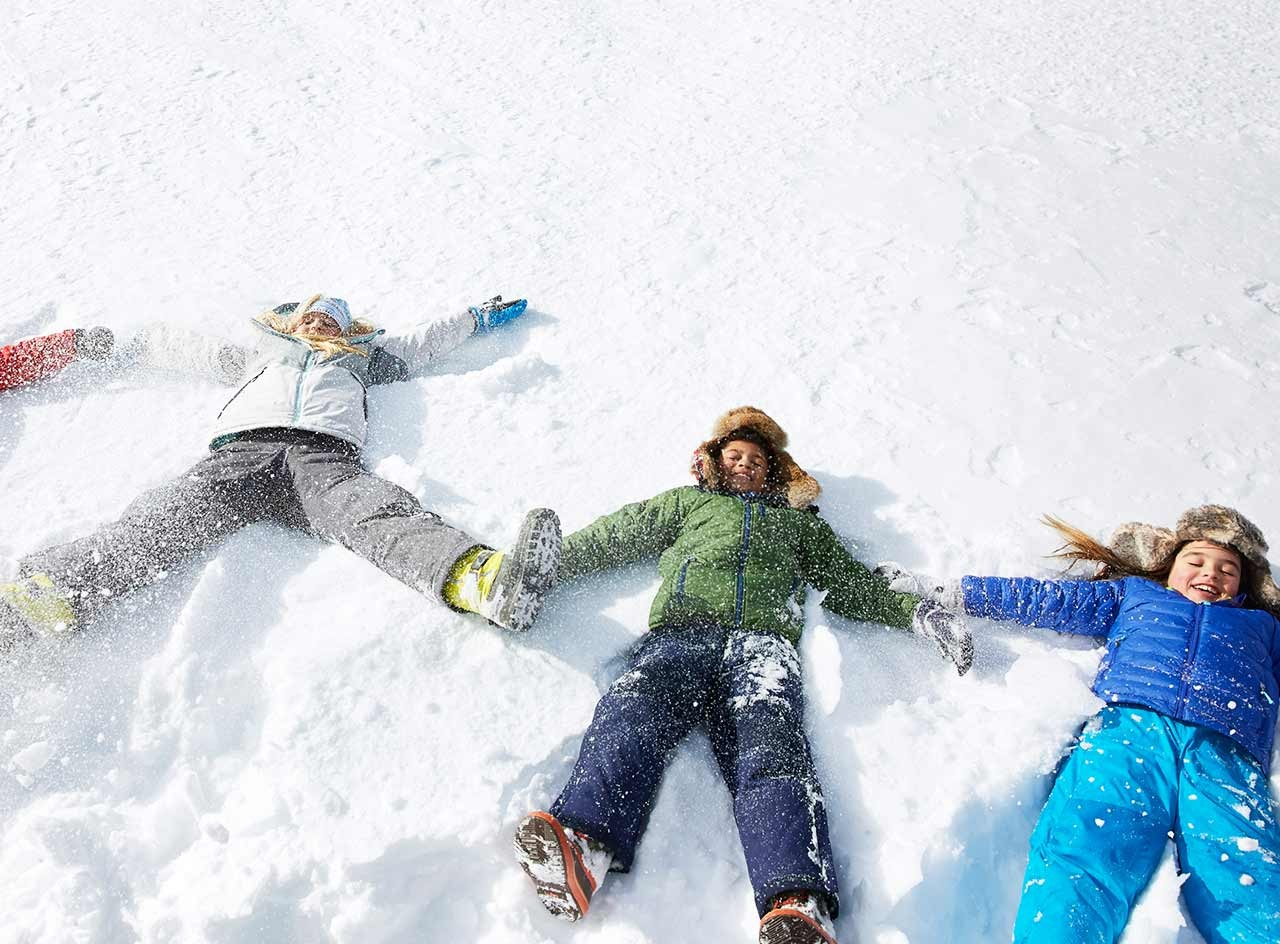 Three children dressed in L.L. Bean snow pants and jackets making snow angels.