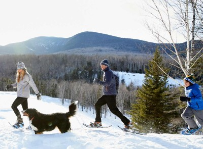 A family snowshoeing with their dog.