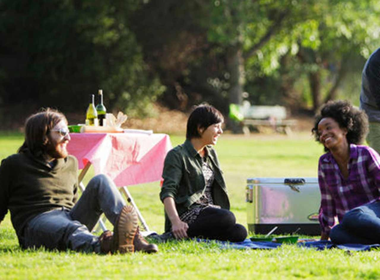 Happy people at a park, having a picnic.
