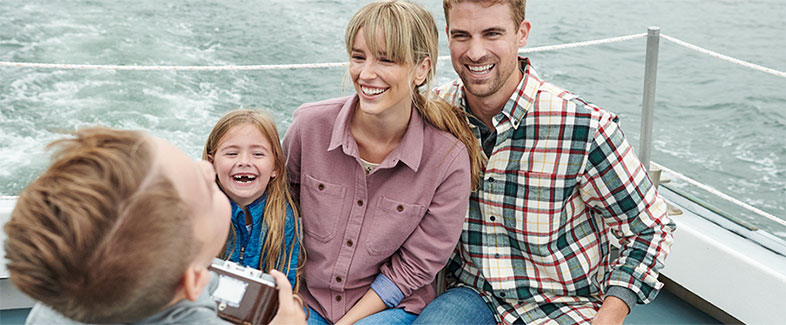 Family enjoying a boating trip in warml flannel layers.