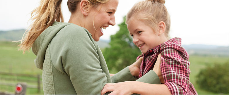 A girl playing with her mom outside wearing L.L.Bean flannel.