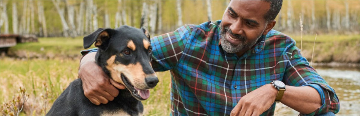 Close-up of man wearing L.L.Bean flannel shirt with arm around dog.