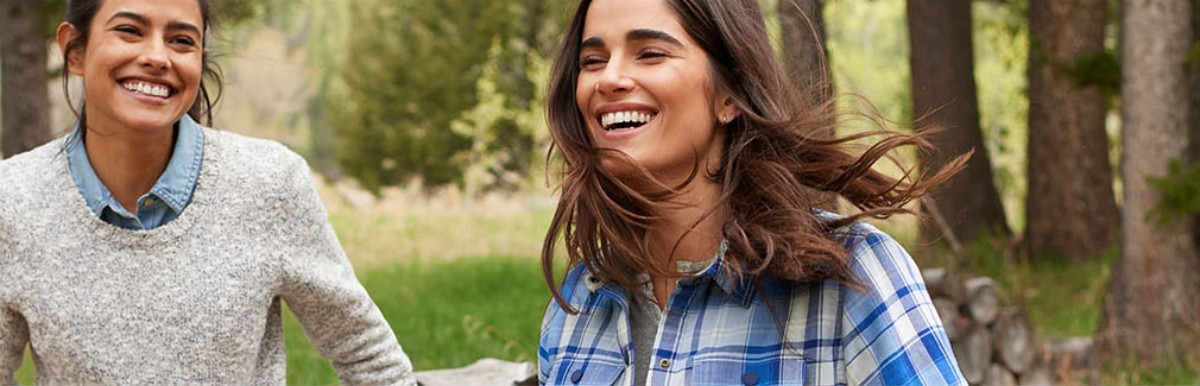 Close-up of 2 smiling women outside, one wearing L.L.Bean flannel shirt.