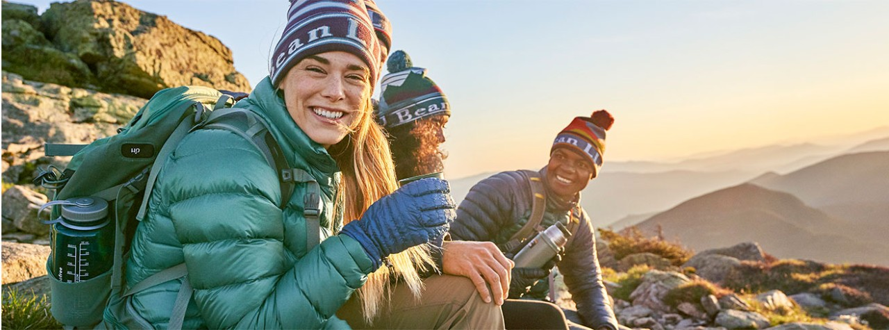 Three hikers enjoying sunrise on a mountain.
