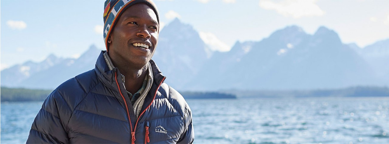A man in cold-weather LLBean outerwear near a lake and mountains.