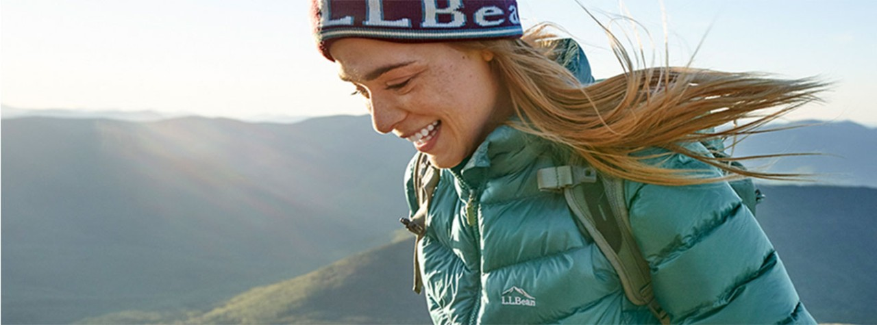 Woman hiking along mountaintops in LLBean cold-weather outerwear.