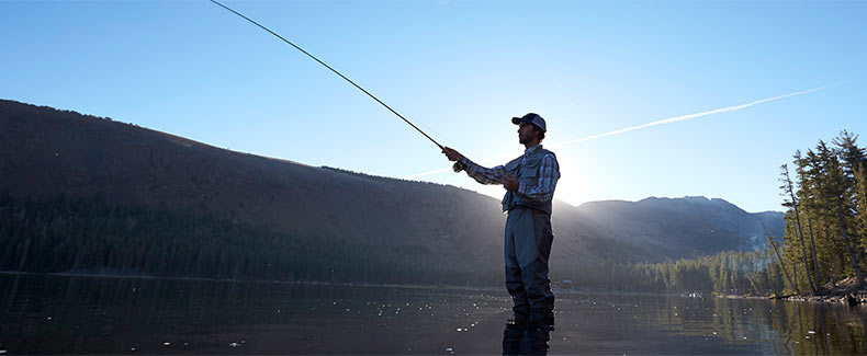 A man casting a fly rod in waders.
