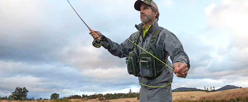 A man fishing with his L.L.Bean vest for flies and tools.