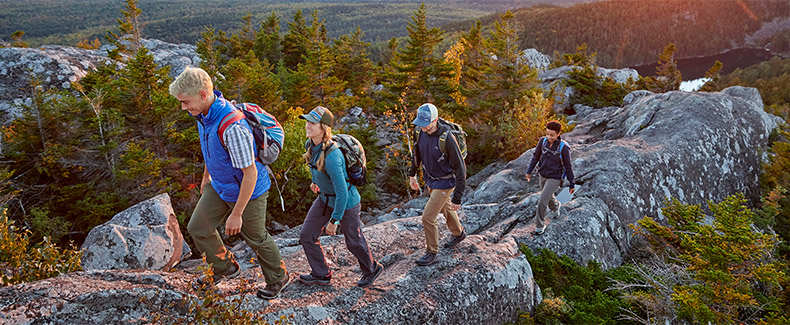 Men and women wearing L.L.Bean clothing, hiking a rock ledge.
