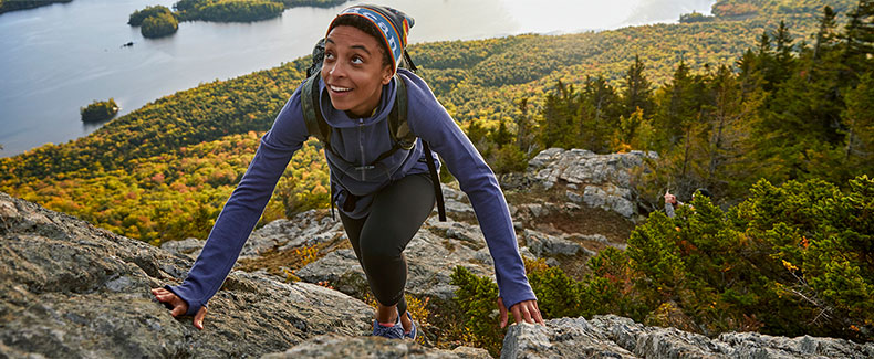 Woman wearing L.L.Bean clothing, hiking up a mountain.