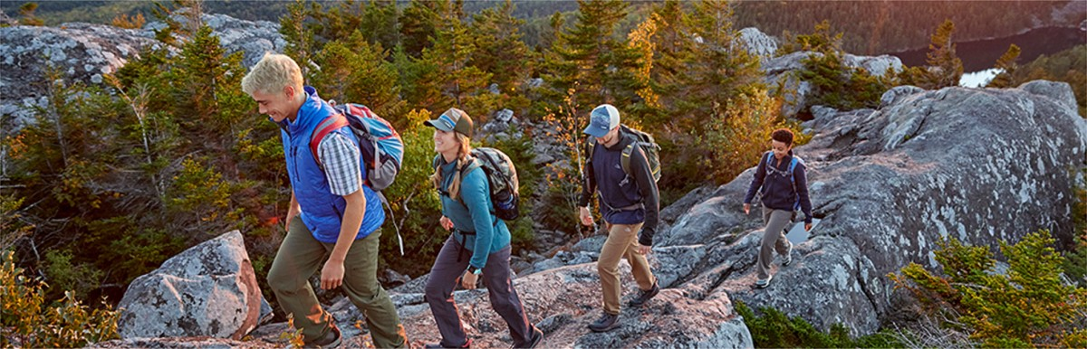Men and women wearing L.L.Bean clothing, hiking up a rock ledge.