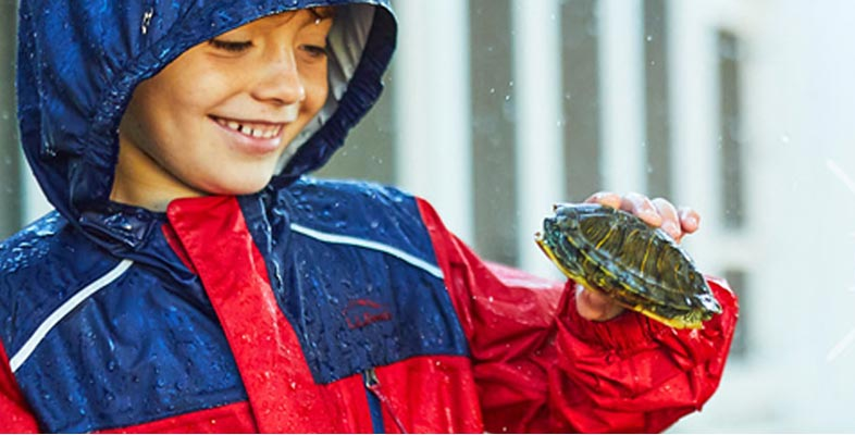 Boy in Trail Model Rain Jacket holding a turtle