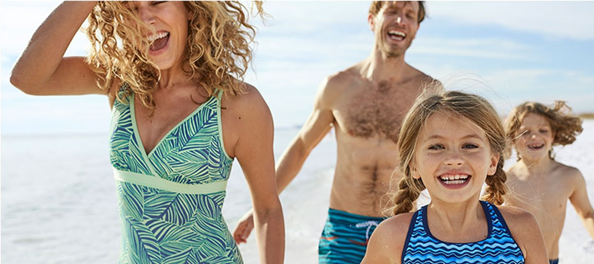 A family playing on a beach in L.L.Bean swimwear.