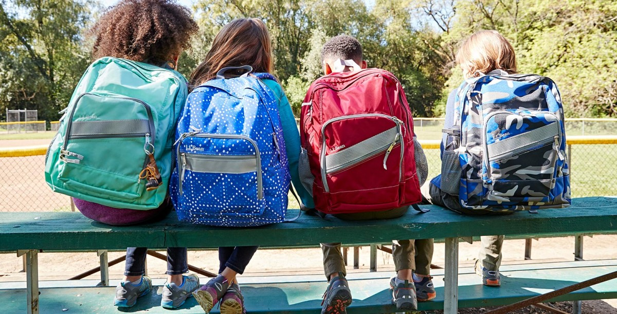 Kids on a bench wearing backpacks