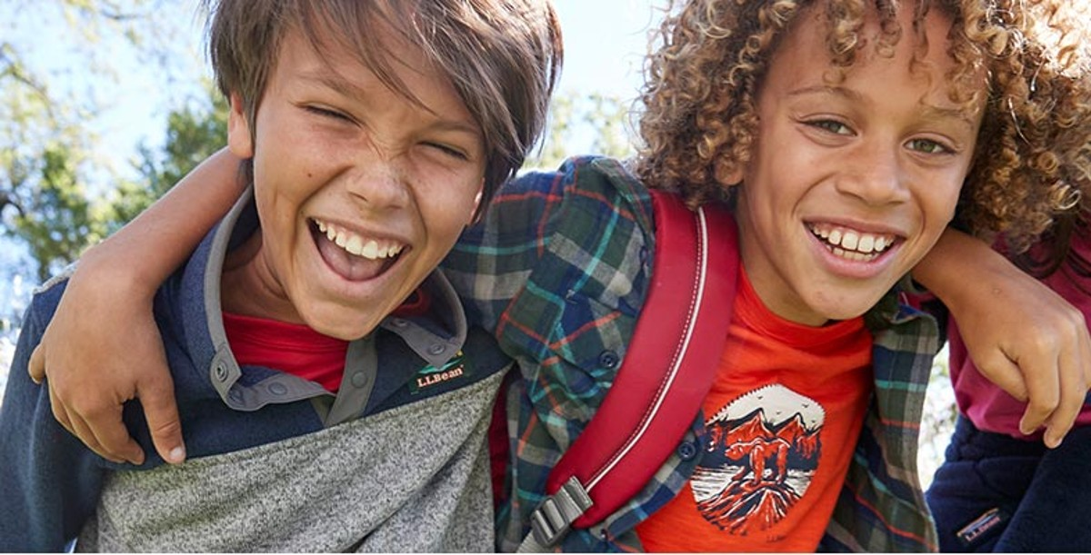Close up of two young boys in L.L.Bean clothing and bookpacks, arms around each other's shoulders, laughing
