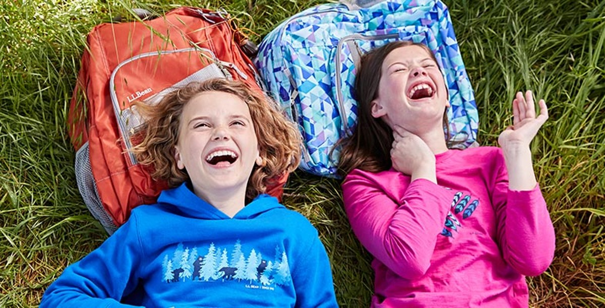 Close up of two young girls wearing L.L.Bean clothing, lying on the grass, heads on bookpacks, laughing.