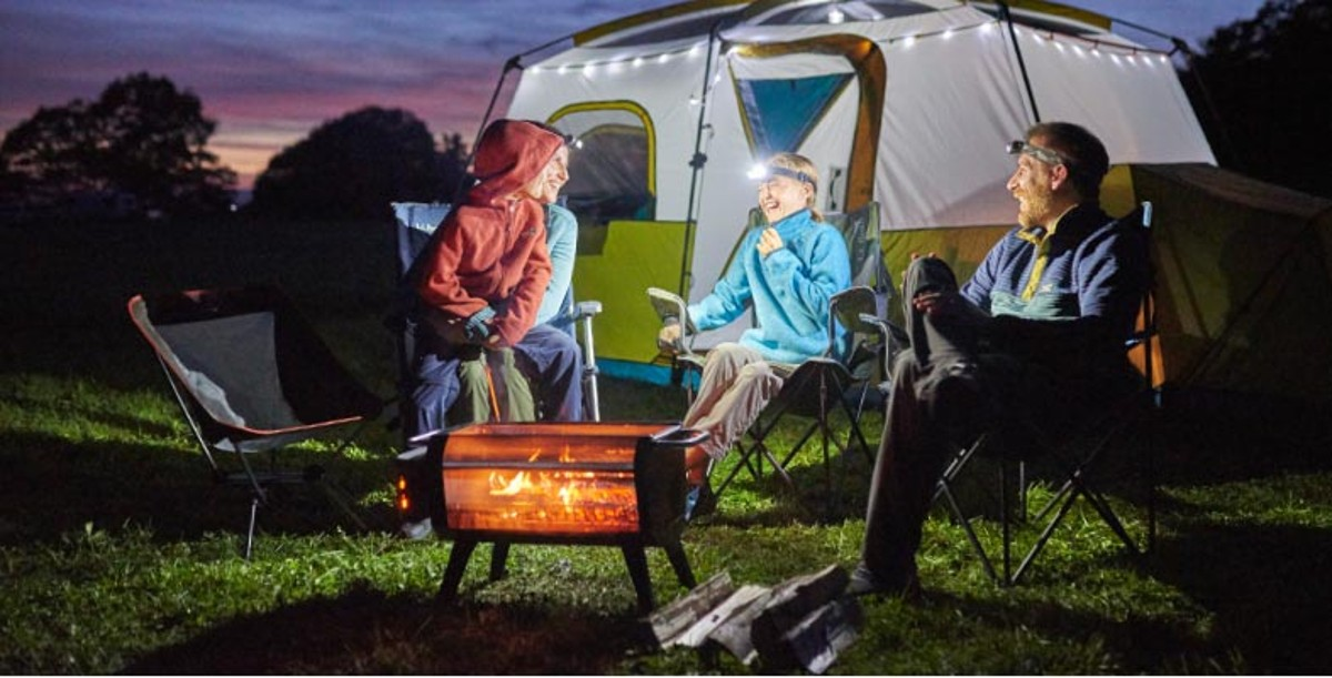 Family enjoying a campfire by their L.L.Bean tent.