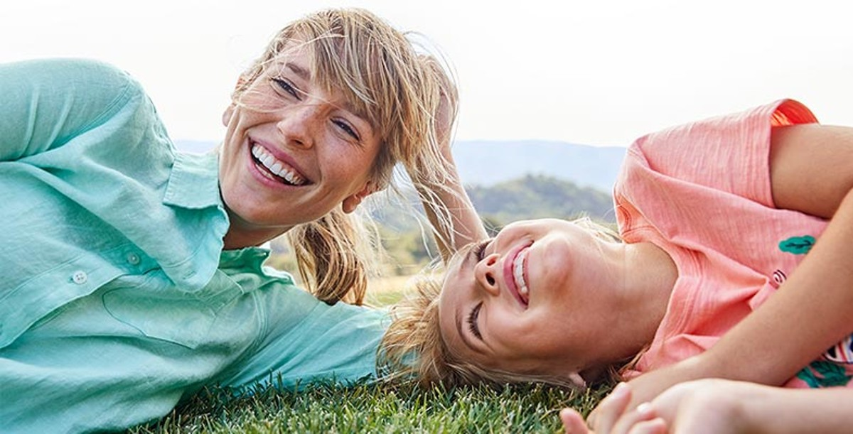 Two women laying in the grass in L.L.Bean shirts