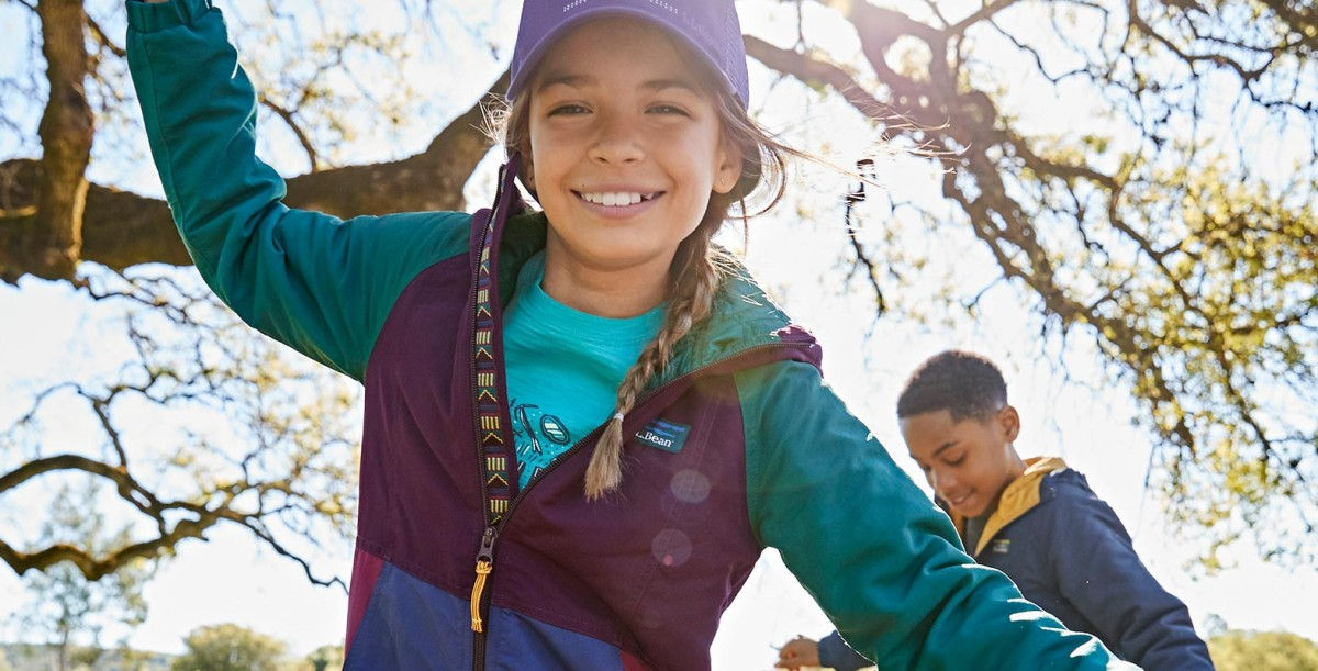Closeup of girl wearing L.L.Bean clothing and anorak, smiling and having fun outdoors with a friend.