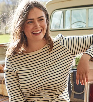 Woman sitting on tailgate wearing L.L.Bean knit striped shirt