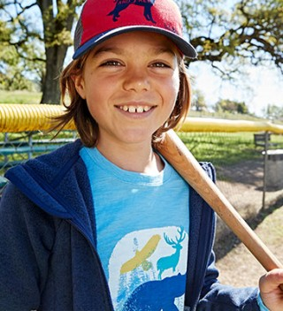 Close-up of boy outside with baseball bat on shoulder wearing ball cap and L.L.Bean apparel