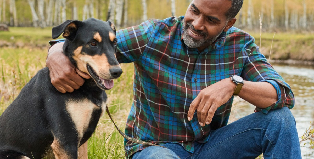 Smiling man, outside, in L.L.Bean Flannel Shirt, crouching with arm around dog.