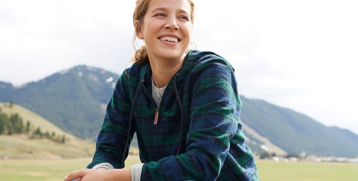 Woman wearing flannel top outside in front of mountain range.
