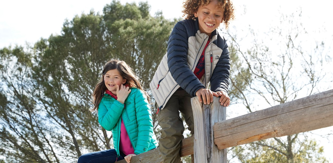 Close-up of happy boy and girl climbing on wooden fence wearing L.L.Bean apparel and outerwear.
