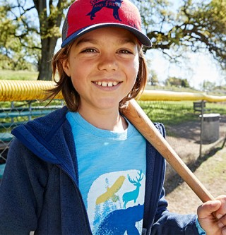 Close-up of boy outside with baseball bat on shoulder wearing ball cap and L.L.Bean apparel.