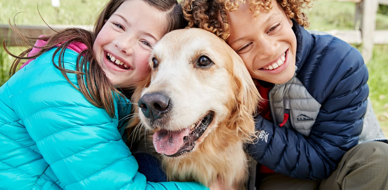 Close up of girl and boy wearing L.L.Bean outerwear, hugging a golden retriever.