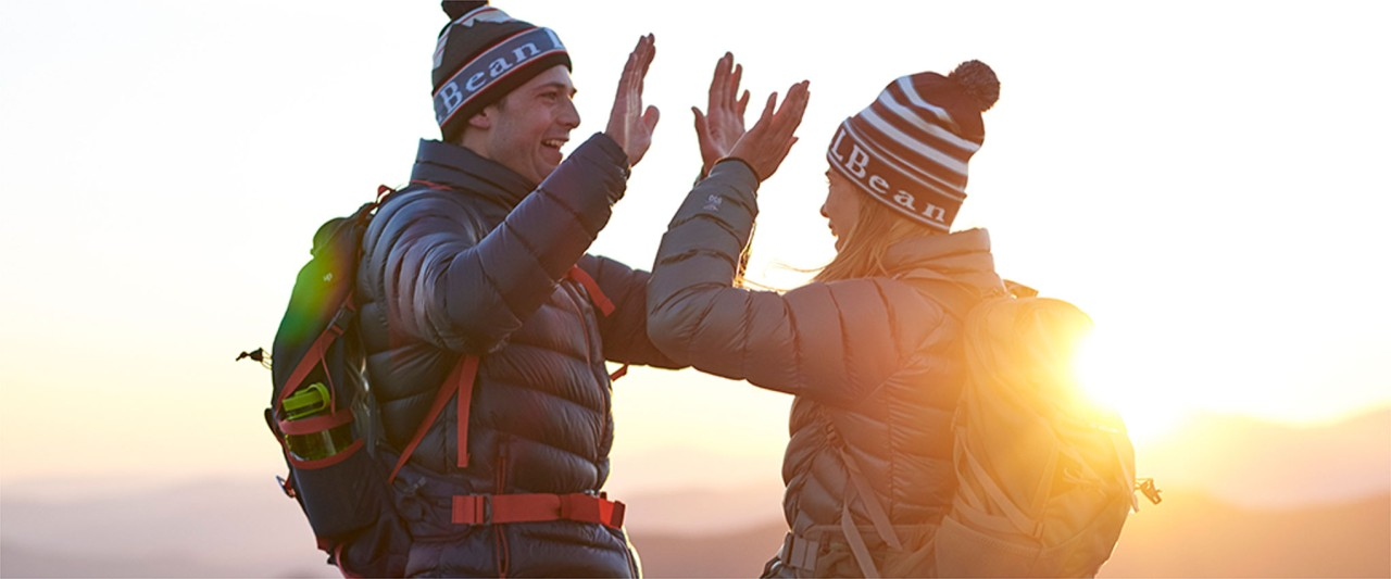 A man and woman hiking on top of a mountain wearing DownTek, knit hats, and backpacks.