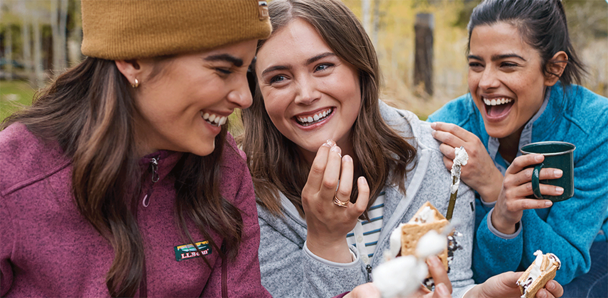 Three women enjoying s'mores and a laugh.