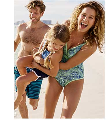 Family running on the beach wearing L.L.Bean swimwear.