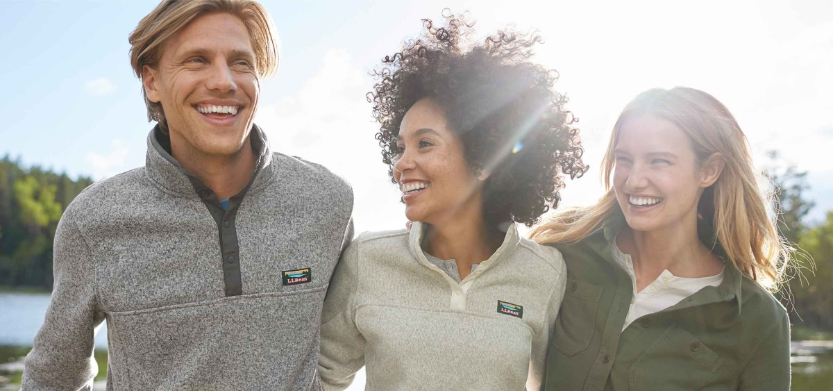 Close up of a man and two women outside, arm-in-arm, smiling, wearing L.L.Bean Sweater Fleece