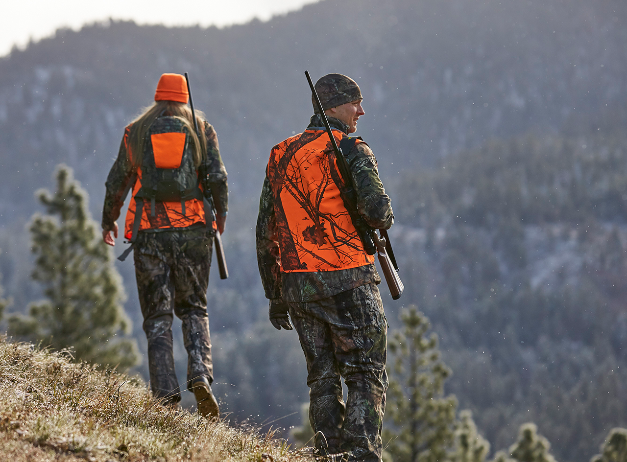 Two hunters in orange safety vests walking on a mountainside.
