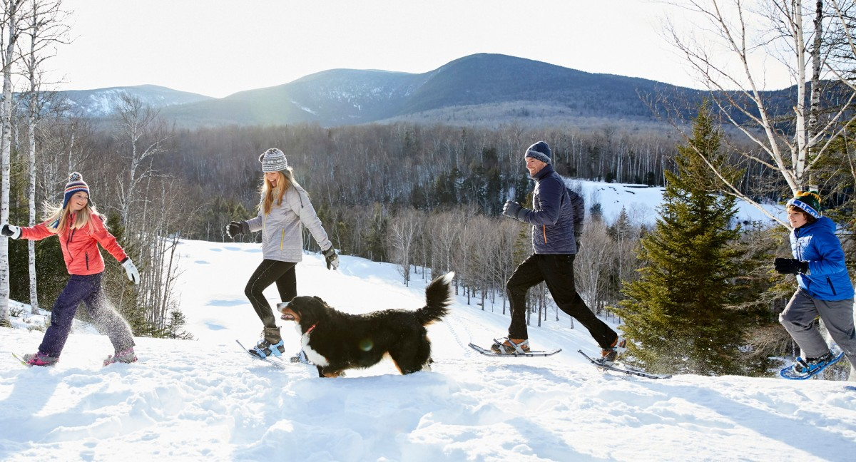 A family and their dog outside enjoying a snowshoe adventure.