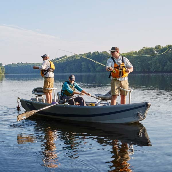 Three men in a boat fly fishing.