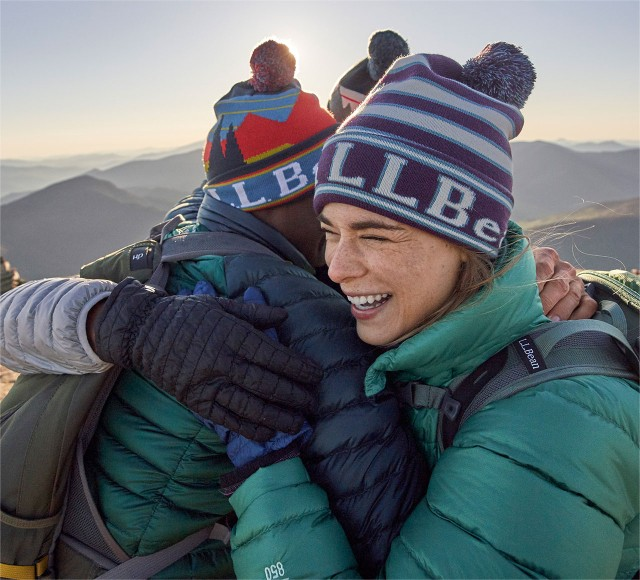 Happy hikers on the trail wearing L.L.Bean Ultralight Down Jackets, in a group hug.