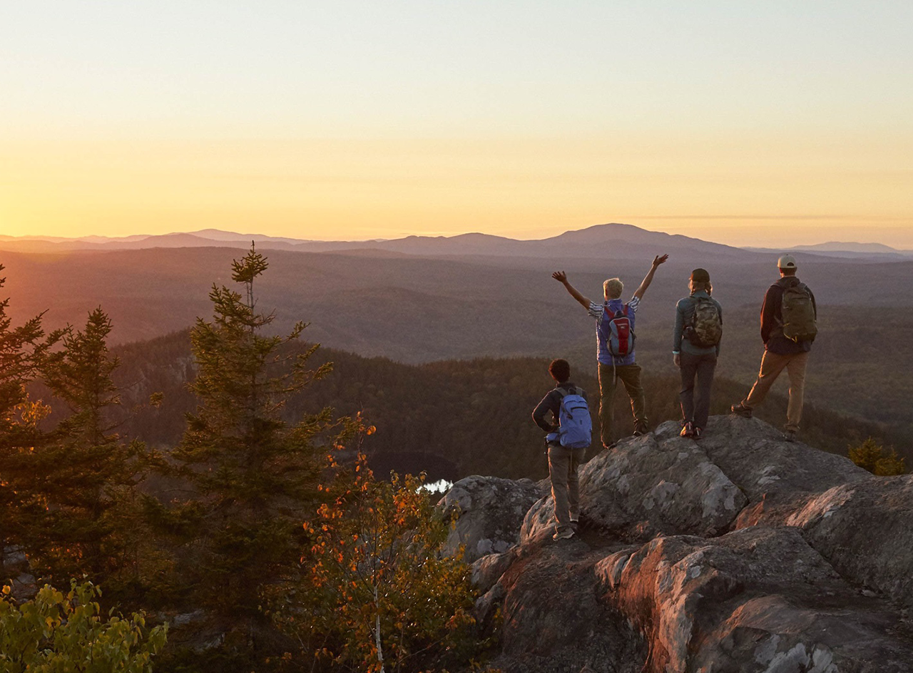 Sunrise with 3 people standing on a mountain top facing the sun