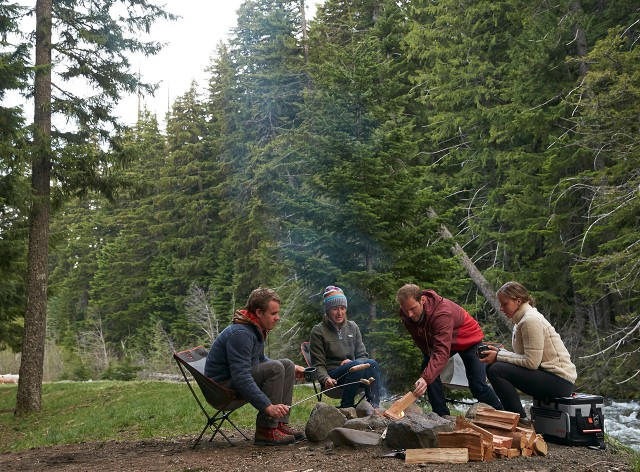4 friends sitting around a campfire by a river.