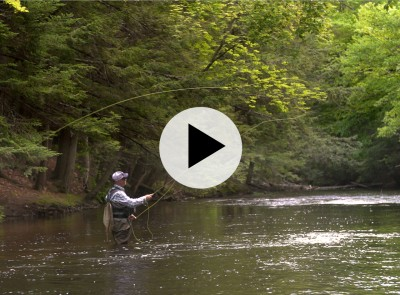 Man standing waist deep in a river fly fishing.