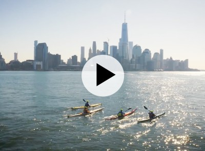 City skyline with four men kayaking in the foreground.