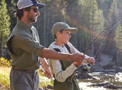 A father teaching a son how to fly fish.