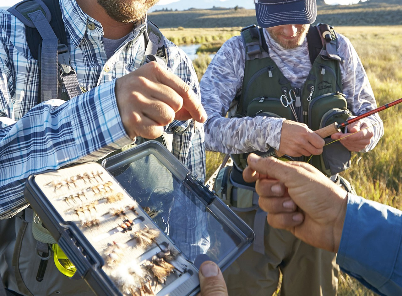 Close up of people picking a fly for a fishing rod.