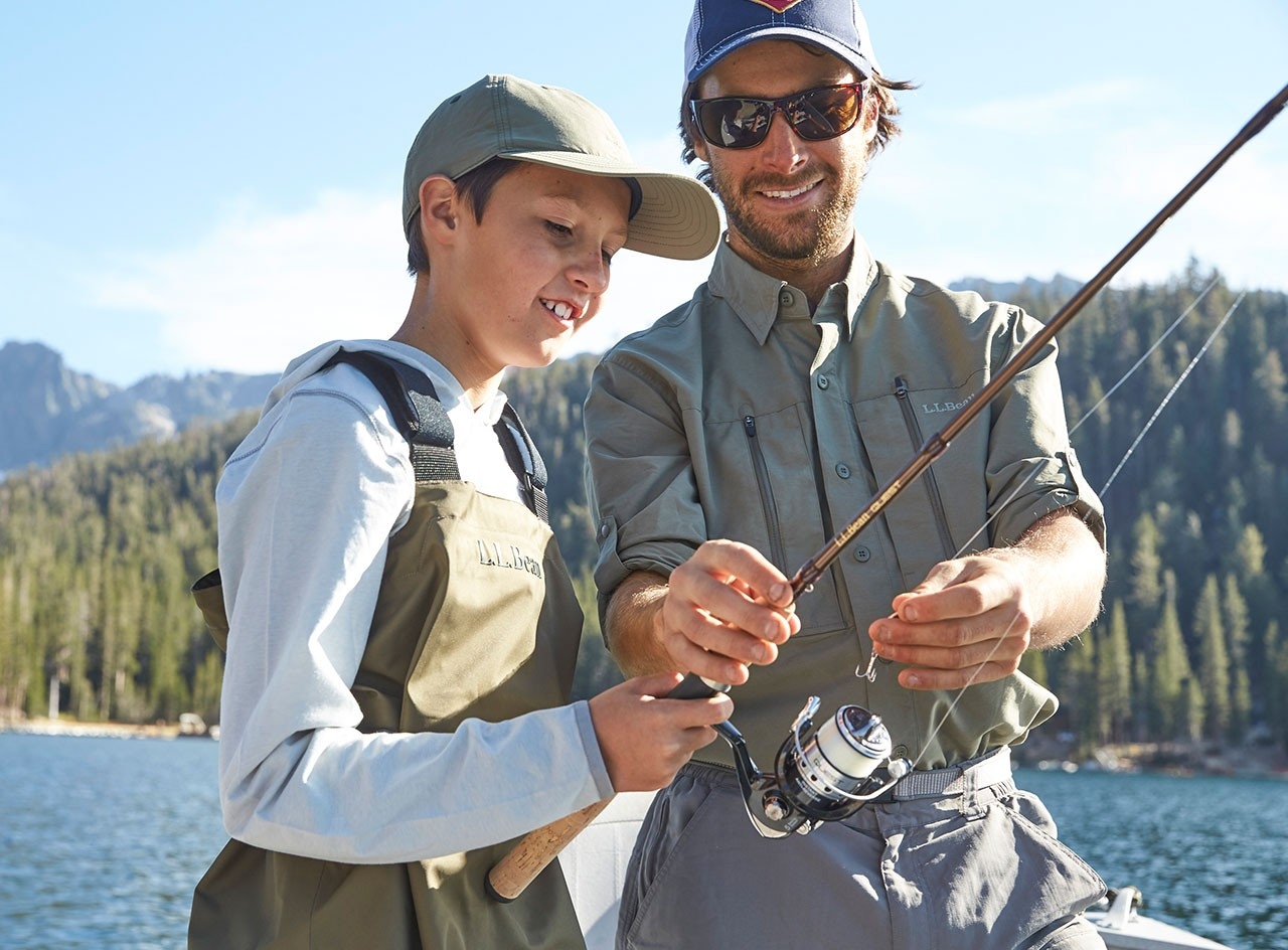 Son and father looking at spin fishing rod.