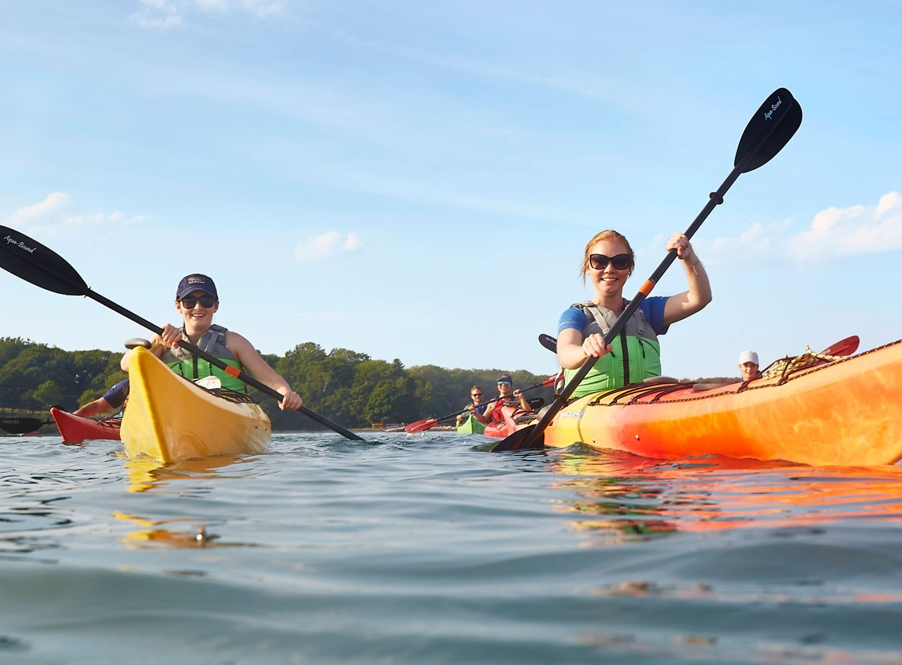 Two smiling people in L.L.Bean kayaks.
