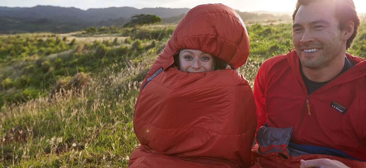 Couple sitting side-by-side on a hillside at sunset, woman zipped up in a sleeping bag with just her smiling face showing.