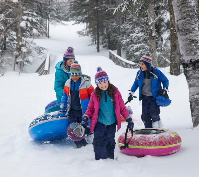 4 kids climbing a sledding hill
